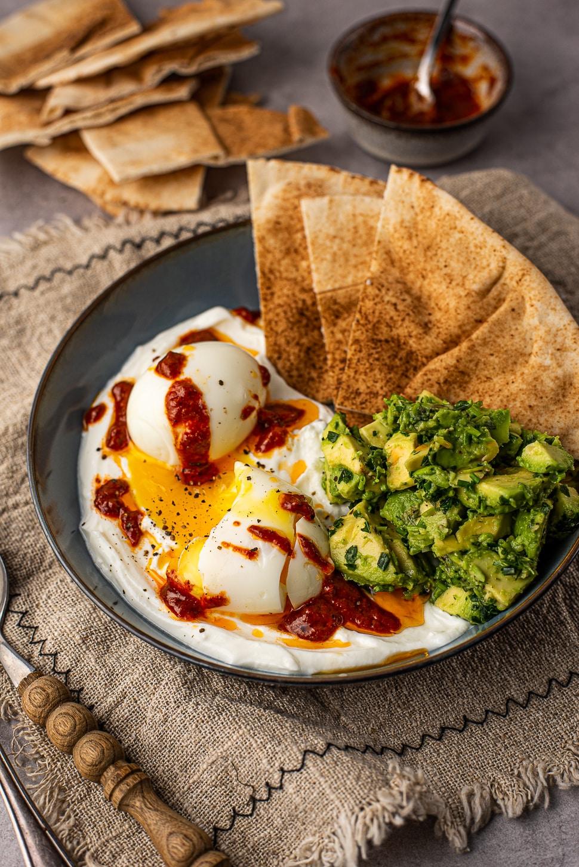 Hartige yoghurtbowl met harissa-eieren en libanees brood